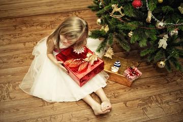 Ребенок с подарками у новогодней елки