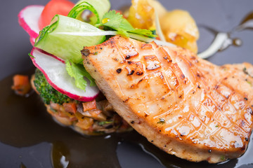 Grilled salmon fillet served with vegetable salad