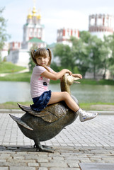 Girl sitting on the big copper duck in the park