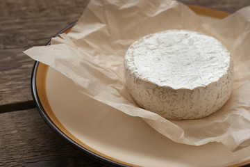 Whole camembert cheese on the white parchment