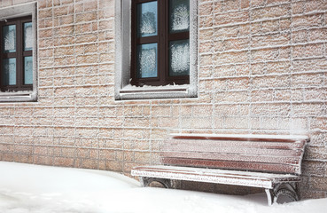Snow-covered bench at  hoarfrost wall of house