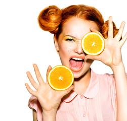 Joyful teen girl with funny red hairstyle. Juicy oranges
