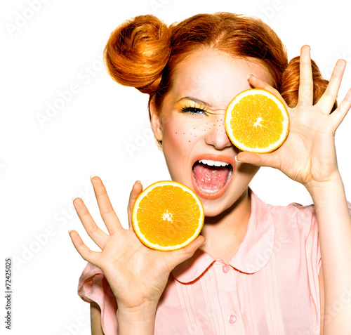 Joyful teen girl with funny red hairstyle. Juicy oranges - 72425025