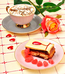 Cap of coffee, a rose and a cake on the tablecloth