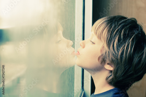 Cute 6 years old boy looking through the window - 72427248