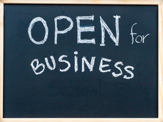 Open for business message handwritten on blackboard