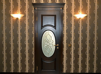 Wooden brown door with a stained-glass window and two wall lamps