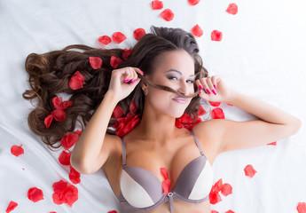 Portrait of funny lingerie model posing in bed