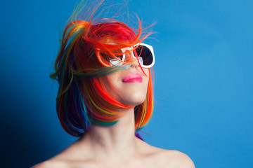 beautiful woman wearing colorful wig and white sunglasses agains