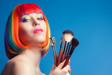 beautiful woman wearing colorful wig and holding make-up brushes