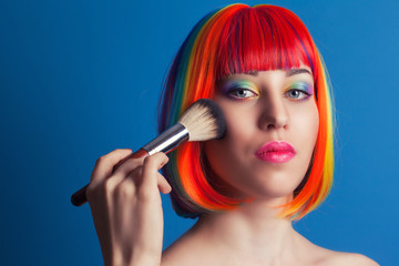 beautiful woman wearing colorful wig and holding make-up brush a