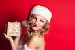 beautiful young woman wearing Santa Claus costume holding gift b