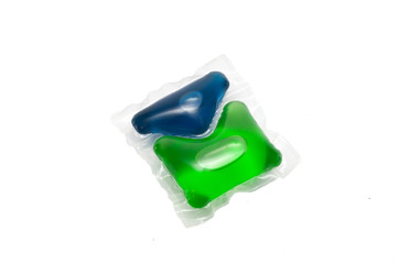 Green and blue gel capsules with laundry detergent on a white ba