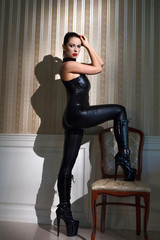 Sexy woman in latex catsuit step on chair