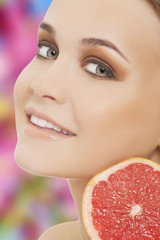 Young brunette with red grapefruit