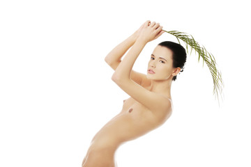 Attractive woman holding a palm leaf