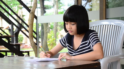 Young girl writing doing homework for school. HD