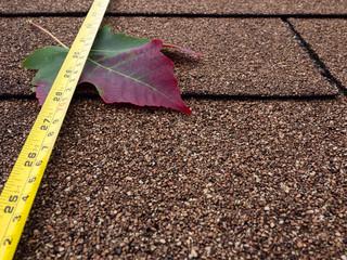 Tape measure and autumn leaf on asphalt shingles