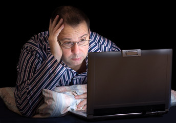 unhappy man with computer in bed