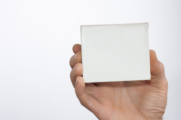 Men's hand with a white packet in a white background