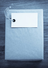paper parcel wrapped tied with price tag on wooden background
