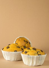 Chocolate chip muffins on brown background with copy space