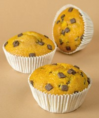 A selection of chocolate chip muffins on a brown background