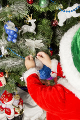 boy decorates a Christmas tree