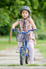 Little Asian child riding a bicycle
