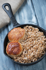 Frying pan with meat cutlets and buckwheat, studio shot