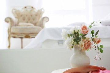 white room interior with bed, window, white roses, pillows