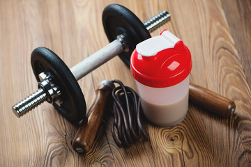Protein shake with a dumbbell and a jumping rope, studio shot