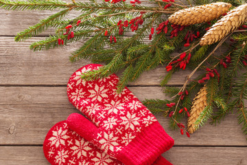 mittens with fir and berry on wooden background