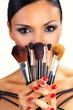 Beautiful black hair girl with makeup brushes.