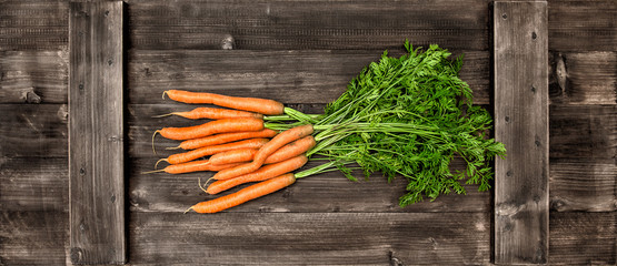 Fresh carrots over wooden background. Vegetable. Food