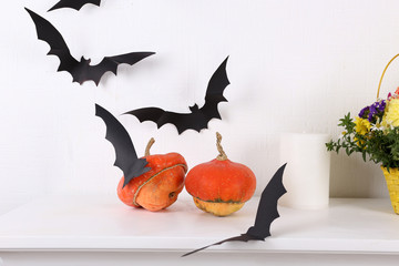Pumpkins with paper bats isolated on white