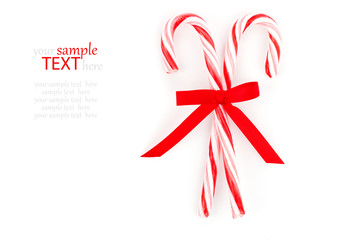 Close up of two candy canes tied with ribbon bow on white backgr