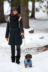 Donna sulla neve con cane bassotto