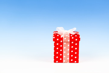 red gift box, polka dots with bow on blue background