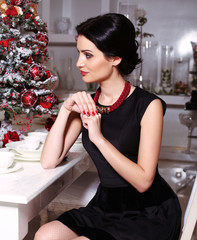 pretty woman sitting beside a decorated Christmas tree
