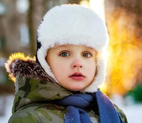 Emotive portrait of little boy in winter clothes. Frosty winter