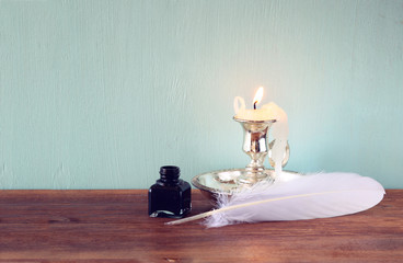 low key image of white Feather, inkwell, and candle on old woode