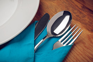 Knife, Fork, Spoon and plate on wooden table.