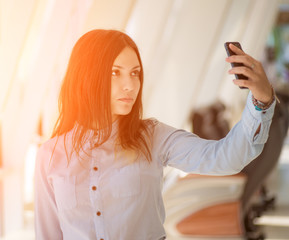 Young woman making selfie. With sunlight.
