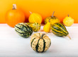 Pumpkins isolated on white wooden table and orange background