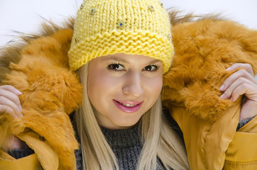 Young girl in winter clothes, wearing cap and jacket with fur