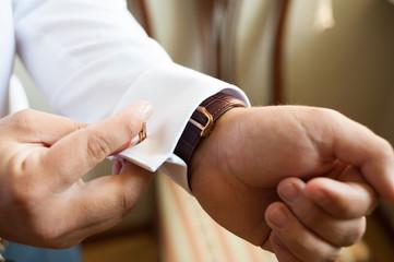 Groom's hands fastening a cufflink