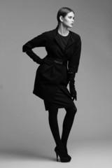 high fashion portrait of elegant woman in black coat. Studio sho