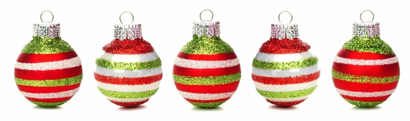 Red green and white Christmas baubles in a row isolated on white