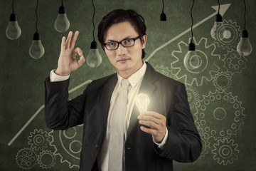 Businessman holding lightbulb with upward graph 2